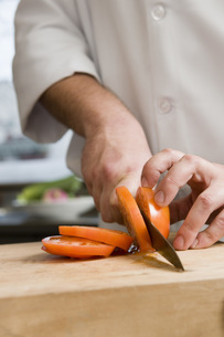 Male chef slicing tomatoの写真素材 [FYI01995667]