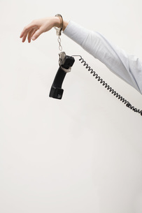 man handcuffed to telephone receiverの写真素材 [FYI01995699]