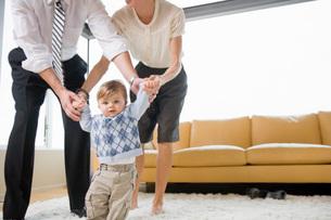 Parents helping baby walkの写真素材 [FYI01995795]