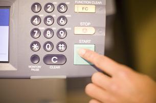 Woman pressing fax machine start buttonの写真素材 [FYI01995879]