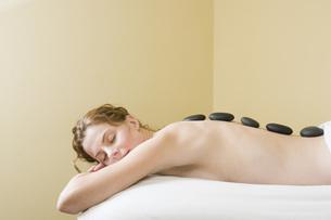 Woman receiving spa stone treatmentの写真素材 [FYI01995886]