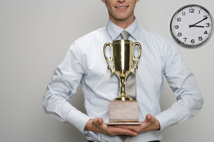 Businessman holding trophyの写真素材 [FYI01996034]
