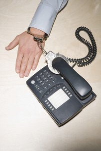 Businessman handcuffed to telephoneの写真素材 [FYI01996039]