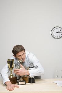 Businessman hugging trophiesの写真素材 [FYI01996042]