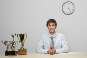 Businessman with trophies on deskの写真素材 [FYI01996301]