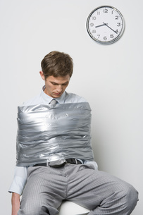 Businessman wrapped in duct tapeの写真素材 [FYI01996303]