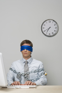 Businessman blindfolded and chainedの写真素材 [FYI01996309]