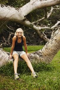 Woman sitting on fallen treeの写真素材 [FYI01996358]