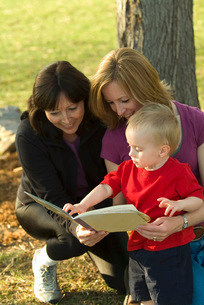 Hispanic grandmother with daughter and grandson reading bookの写真素材 [FYI01996422]
