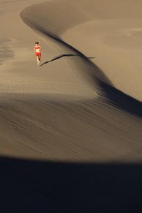 Woman running on sand dunesの写真素材 [FYI01996442]