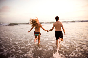 Couple holding hands and running through surfの写真素材 [FYI01996458]