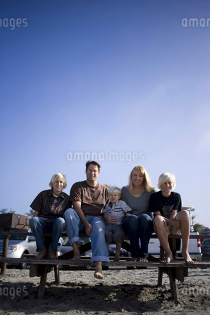 Family sitting on table at beachの写真素材 [FYI01996459]