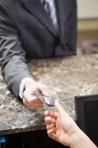 Businessman paying at hotel front deskの写真素材 [FYI01996513]
