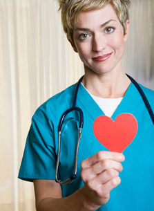 Female nurse holding heart-shaped cut outの写真素材 [FYI01996552]