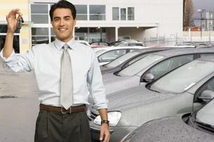 Man holding car keys at car dealershipの写真素材 [FYI01996572]