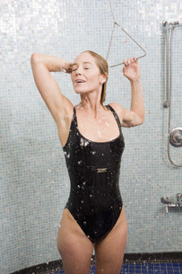 Woman in bathing suit taking showerの写真素材 [FYI01996588]