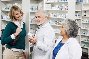 Pharmacists explaining medication to customerの写真素材 [FYI01996596]