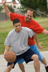 Hispanic men playing basketballの写真素材 [FYI01996633]