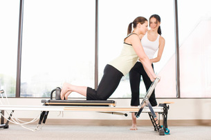 Personal trainer guiding woman on pilates equipmentの写真素材 [FYI01996687]