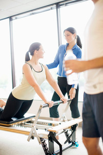 Personal trainer guiding woman on pilates equipmentの写真素材 [FYI01996695]