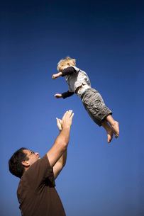 Father tossing son in airの写真素材 [FYI01996696]