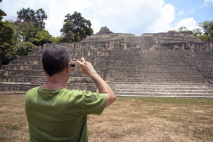 Man taking photo of Caana structure,Caracol,Belizeの写真素材 [FYI01996700]