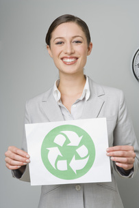 Businesswoman holding recycling signの写真素材 [FYI01996729]