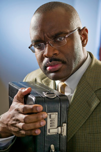 Serious African American businessman clutching briefcaseの写真素材 [FYI01996735]
