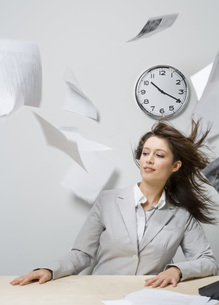 Wind blowing on businesswoman at deskの写真素材 [FYI01996737]