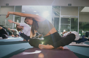 Woman stretching in yoga classの写真素材 [FYI01996746]