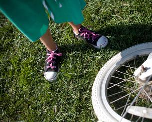 Childis feet next to bicycle wheelの写真素材 [FYI01996747]