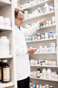 Pharmacist looking at prescriptionの写真素材 [FYI01996760]