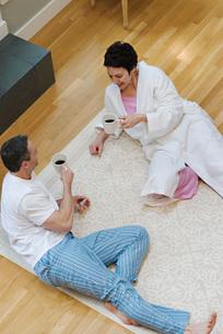 Couple laying on floor drinking coffeeの写真素材 [FYI01996776]