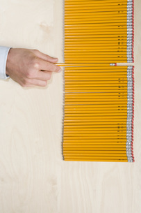Hand pulling pencil out of rowの写真素材 [FYI01996784]