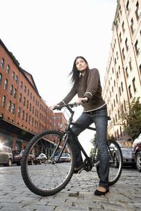Hispanic woman standing with bicycleの写真素材 [FYI01996791]