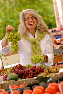Woman holding grapes at outdoor marketの写真素材 [FYI01996821]