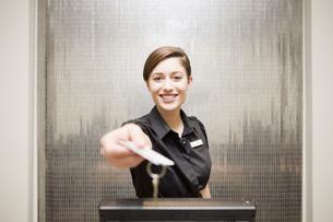 hotel front desk clerk handing keycardの写真素材 [FYI01996822]