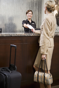 woman checking in at hotel front deskの写真素材 [FYI01996851]