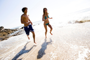 Multi-ethnic couple running on beachの写真素材 [FYI01996876]