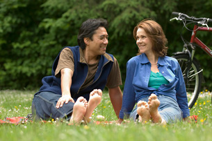 Couple sitting barefoot in parkの写真素材 [FYI01996889]