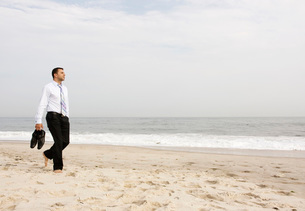 Businessman walking barefoot on beachの写真素材 [FYI01996927]
