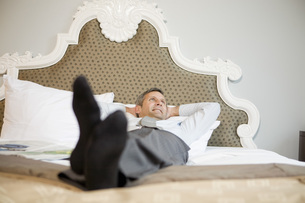 Businessman laying on bedの写真素材 [FYI01996940]