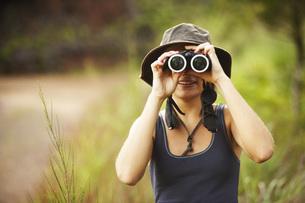 Woman looking through binocularsの写真素材 [FYI01996941]