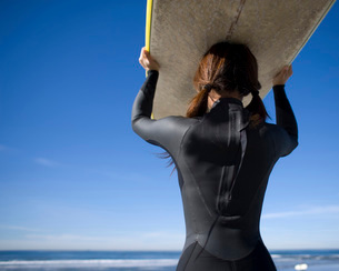 Female surfer carrying surfboardの写真素材 [FYI01996959]
