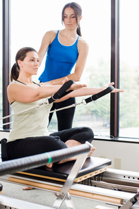 Personal trainer guiding woman on pilates equipmentの写真素材 [FYI01996963]