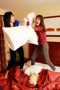 Multi-ethnic women having pillow fightの写真素材 [FYI01996965]