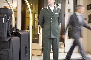 Bellhop standing next to luggage cartの写真素材 [FYI01996997]