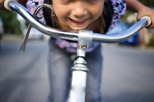 Girl leaning over bicycle handlebarsの写真素材 [FYI01997017]