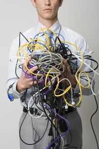 man holding tangle of computer wiresの写真素材 [FYI01997026]