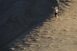 Woman running on sand dunesの写真素材 [FYI01997037]